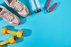 Female sport shoes and equipment top view, copy space. Active lifestyle, body care concept. Female sport shoes and equipment on a bright blue background. Active royalty free stock photos
