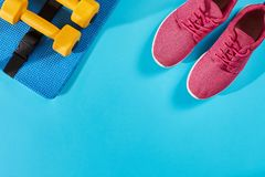Female sport shoes and equipment top view, copy space. Active lifestyle, body care concept. Female sport shoes and equipment on a bright blue background. Active royalty free stock photo