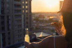 A female in a sport suit holds a huge piece of pizza and a bottle of mojito on sunset light. Concept royalty free stock photography