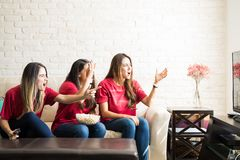 Sports fans rooting for their team. Female sports fans watching a game and rooting for their team wearing the same jersey Royalty Free Stock Photography