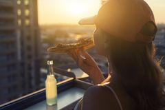 A female in a sports suit eats a huge piece of pizza on sunset and city background. A female in a sports suit eatss a huge piece of pizza on sunset and city royalty free stock photo