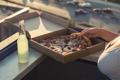 A female in a sports suit holds a huge piece of pizza on sunset and city background. A female in a sports suit with beautiful breast holds a piece of pizza and a stock photo