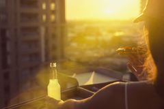 A female in a sports suit holds a huge piece of pizza on sunset and city background. A female in a sports suit holds a huge piece of pizza and a bottle of mojito royalty free stock photos