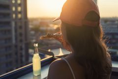 A female in a sports suit with a huge piece of pizza and a bottle of mojito on sunset and city background. Concept royalty free stock photo