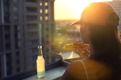 A female in a sports suit with a huge piece of pizza and a bottle of mojito on sunset and city background. Concept royalty free stock photography