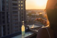 A female in a sports suit with a huge piece of pizza and a bottle of mojito on sunset and city background. Concept stock photography