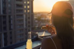 A female in a sports suit with a huge piece of pizza and a bottle of mojito on sunset and city background. Concept royalty free stock images