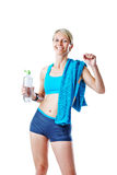 Female in sports wear happy after workout refreshing herself with water and smiling to the camera Royalty Free Stock Photography