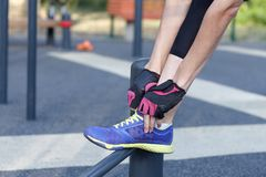 Female in sportswear and protective gloves ties bright sneakers preparing for a jog, run or other fitness. Morning workout on outd. Oors background. Copy space stock photos