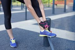 Female in sportswear and protective gloves ties bright sneakers preparing for a jog, run or other fitness. Morning workout on outd. Oors background. Copy space stock photography