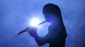 Female in spotlight in smoky studio plays on flute, silhouette. Female in spotlight in smoky studio plays on flute, dark silhouette of girl in smoke is visible stock video footage