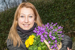 Female with spring flowers. Female holding a basket with spring flowers Stock Photography