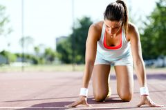 Female sprinter getting ready for the run. Beautiful female sprinter getting ready for the run during summer Royalty Free Stock Photos