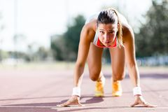 Female sprinter getting ready for the run. Beautiful female sprinter getting ready for the run during summer Stock Photography