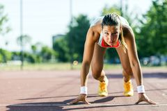 Female sprinter getting ready for the run. Beautiful female sprinter getting ready for the run during summer Stock Photo