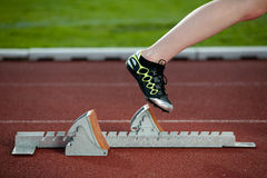 Female sprinter leaving starting blocks Stock Photos