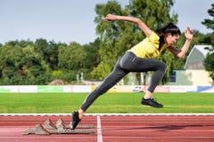 Female sprinter leaving starting blocks on running track Stock Photography