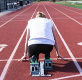 Female sprinter in the starting blocks from behind royalty free stock images