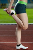 A female sprinter stretching. On the running track - side view Royalty Free Stock Photo