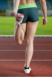 A female sprinter stretching Royalty Free Stock Photos