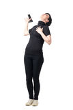 Female spy in black clothes falling backwards and dropping gun while getting shot. Full body length portrait isolated over white studio background royalty free stock image