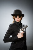 The female spy with weapon against gray Stock Photography