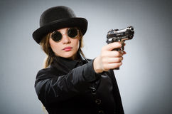 The female spy with weapon against gray Stock Photos