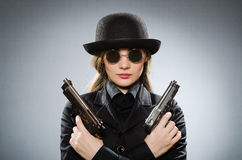 The female spy with weapon against gray Stock Images