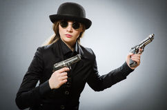 The female spy with weapon against gray. Female spy with weapon against gray Royalty Free Stock Photos