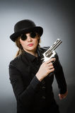 The female spy with weapon against gray Royalty Free Stock Image