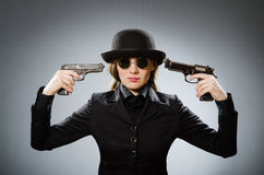 The female spy with weapon against gray Royalty Free Stock Photo