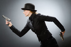 The female spy with weapon against gray Stock Image