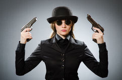 Female spy with weapon against gray Royalty Free Stock Photo