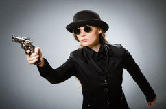 The female spy with weapon against gray Royalty Free Stock Images