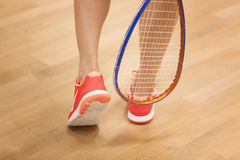 Female squash player hiting a ball in a squash court Royalty Free Stock Photos
