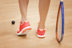 Female squash player hiting a ball in a squash court Stock Photo