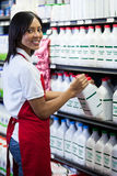 Female staff arranging milk bottle in shelf. Portrait of female staff arranging milk bottle in shelf at dairy section of supermarket royalty free stock photos