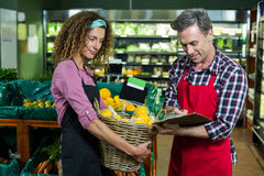 Female staff holding basket of fruit and male staff writing on clipboard. In supermarket Royalty Free Stock Image