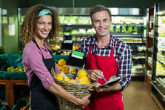 Female staff holding basket of fruits and male staff with clipboard in supermarket. Portrait of female staff holding basket of fruits and male staff with Royalty Free Stock Image