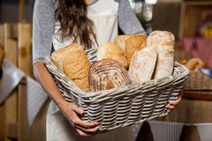 Female staff holding wicker basket of various breads at counter in bakery shop Stock Image