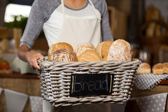 Female staff holding wicker basket of various breads at counter in bakery shop Royalty Free Stock Photo