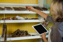 Female staff maintain records of meat on digital tablet at counter Stock Image