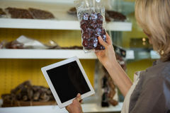 Female staff maintain records of meat on digital tablet at counter Royalty Free Stock Photo