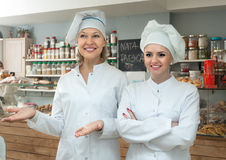 Female staff offering sweets in local confectionery. Friendly female staff offering sweets in lconfectionery royalty free stock photo