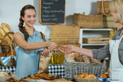 Female staff receiving a payment from customer at counter Royalty Free Stock Image