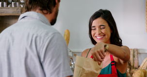 Female staff serving bread at bakery store. In supermarket stock footage