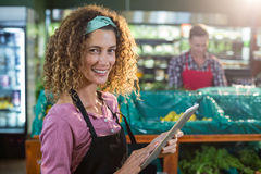 Female staff using digital tablet in organic section. Portrait of smiling female staff using digital tablet in organic section of supermarket Royalty Free Stock Images