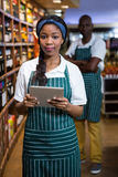 Female staff using digital tablet in organic section Stock Photos