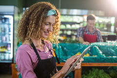 Female staff using digital tablet in organic section. Smiling female staff using digital tablet in organic section of supermarket Stock Image