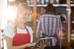 Female staff using digital tablet in supermarket. Smiling female staff using digital tablet in supermarket Royalty Free Stock Images